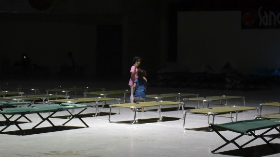 Two girls play on cots at the Humacao Arena.