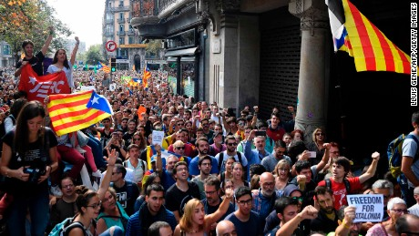 People holding Catalan flags demonstrate outside the regional government's economic headquarters on Wednesday during a police operation.