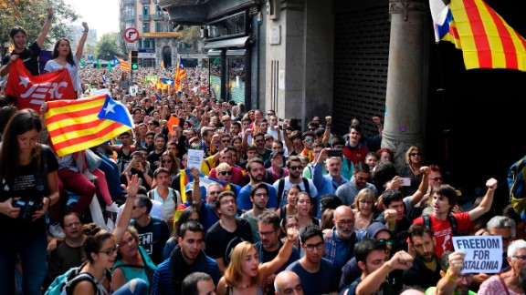 People holding Catalan flags demonstrate outside the regional government
