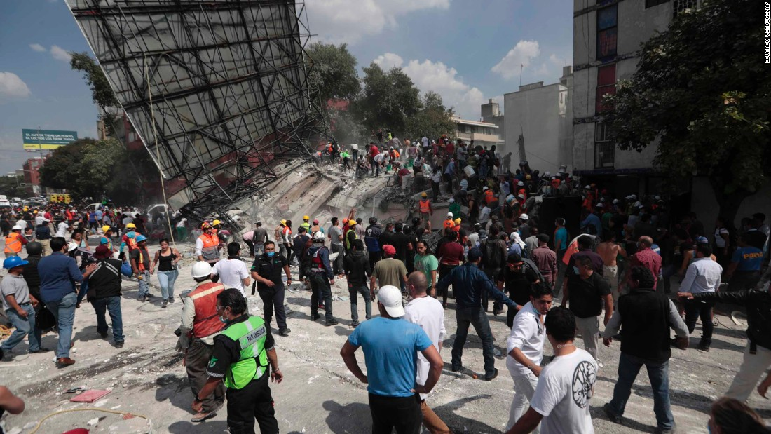 Rescue workers and volunteers search a collapsed building in Mexico City on September 19.