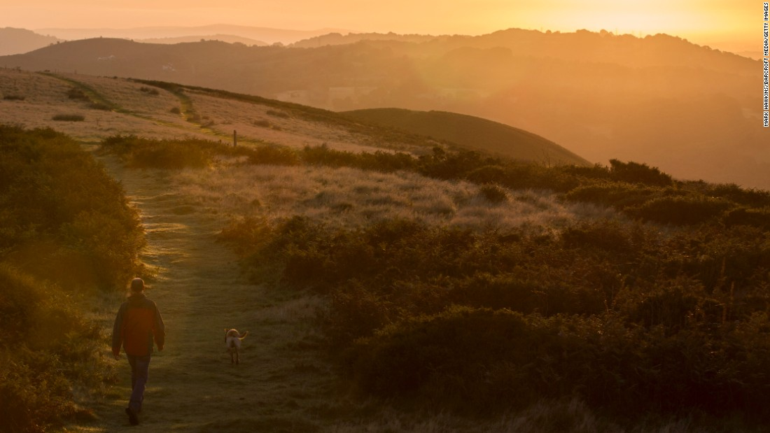 <strong>Pentyrch, UK: </strong>A man and his dog walk at dawn through the Welsh countryside on the first day of September.