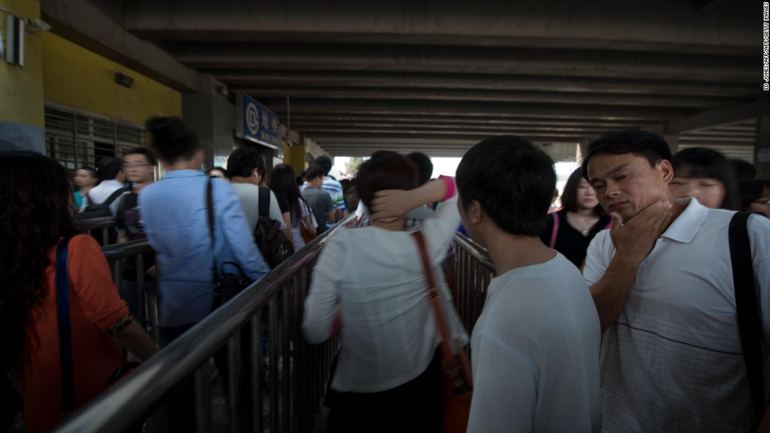 Commuters wait to enter a subway station during the morning rush hour in Beijing. Despite some five million private vehicles in Beijing, public transport faces heavy congestion on a daily basis as most of the city's 21.5 million people head to work.