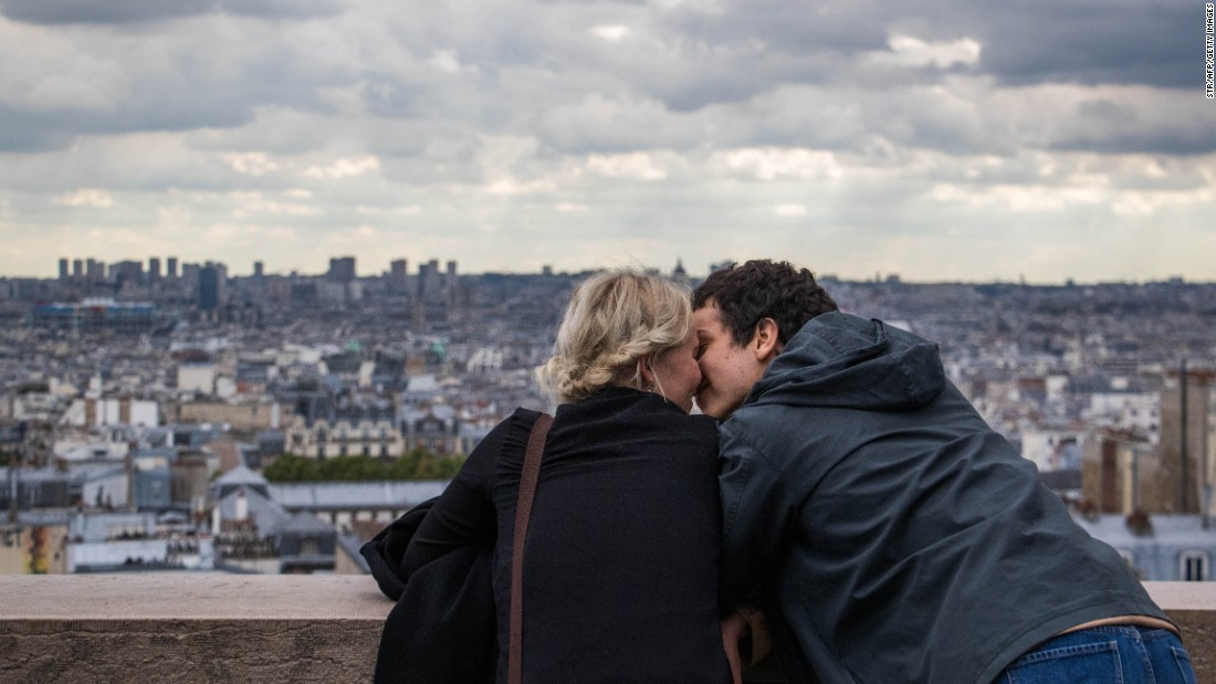 <strong>Paris: </strong>Tourists kiss as they take in the view from outside the Sacré-Coeur Basilica in Montmartre.