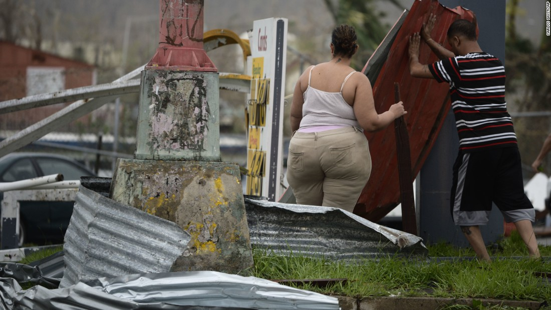 Residents move aluminum panels from an intersection in Humacao on September 20.
