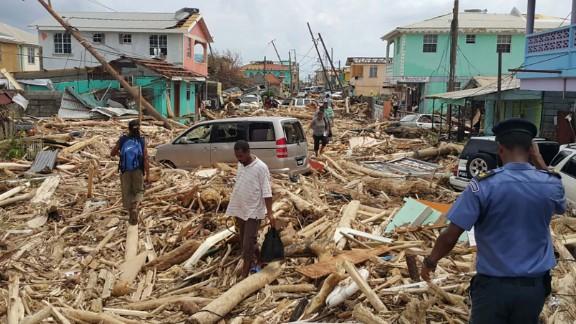 People walk through the destruction in Roseau on September 20.