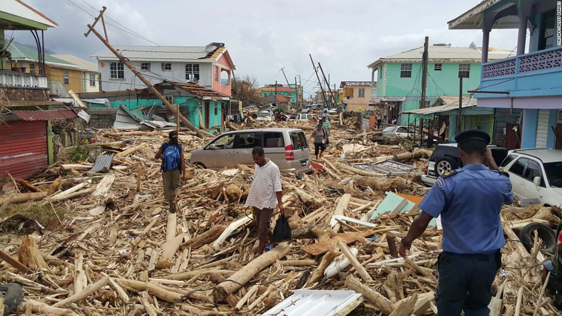 People walk through the destruction in Roseau on September 20.