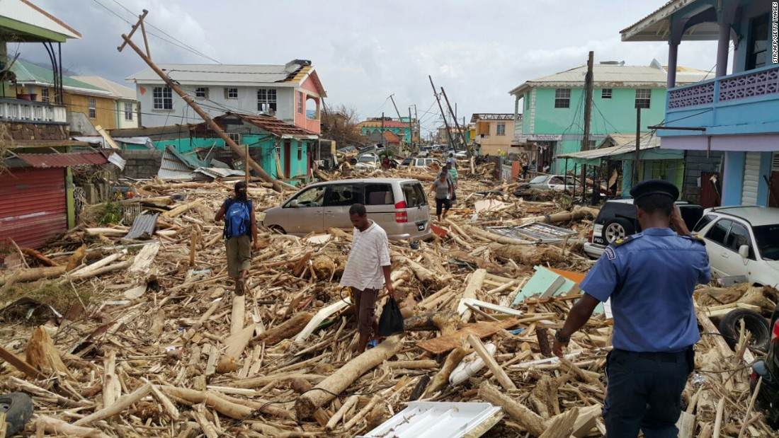 "People walk amid debris in Roseau, Dominica, on Wednesday, September 20. Hurricane Maria <a href=""http://www.cnn.com/2017/09/20/world/hurricane-maria-dominica/index.html"" target=""_blank"">battered the Caribbean island.</a> A CNN crew that flew over its scarred landscape witnessed heartbreaking devastation."