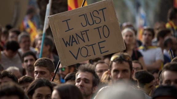 "A banner reading ""I just want to vote"" is seen as demonstrators gather outside the Catalan high court."