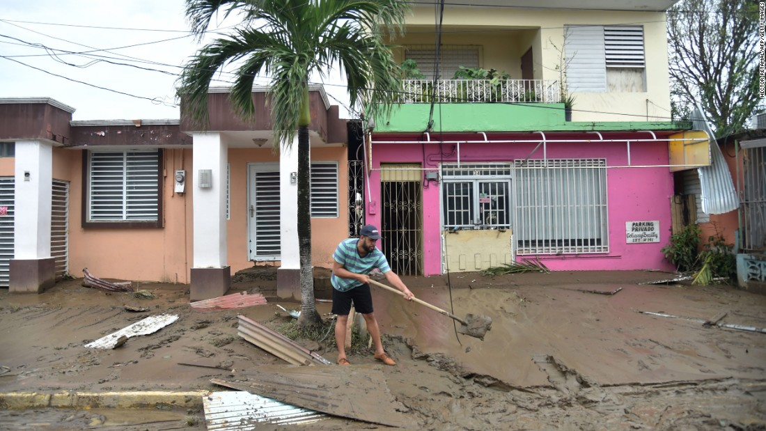 A man cleans a muddy street in Toa Baja, Puerto Rico, on September 22.