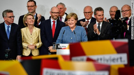 German Chancellor and Christian Democrat (CDU) Angela Merkel (C) reacts to initial results that give the party 32,9% of the vote, giving it a first place finish, in German federal elections on September 24, 2017 in Berlin, Germany. Chancellor Merkel is seeking a fourth term and coming weeks will likely be dominated by negotiations between parties over the next coalition government.