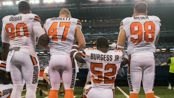 Cleveland Browns players take a knee and join arms during a game against the Indianapolis Colts.