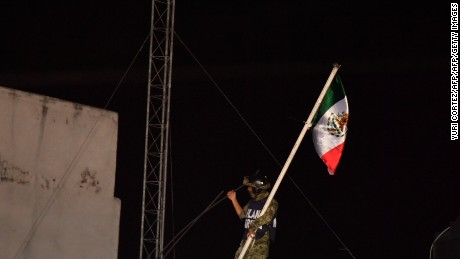 A Mexican marine places the national flag over a collapsed building as rescue workers continue to search for survivors as night falls in Mexico City on September 22, 2017, three days after the powerful quake that hit central Mexico, causing panic among the megalopolis' 20 million inhabitants on the 32nd anniversary of a devastating 1985 quake. / AFP PHOTO / YURI CORTEZ        (Photo credit should read YURI CORTEZ/AFP/Getty Images)