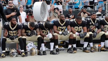 New Orleans Saints players sit on the bench during the national anthem before a game against the Carolina Panthers.
