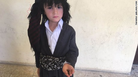 "Six-year old Hedad holds three rocks, each representing ""divorce"" from Iraq."