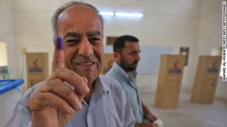 An Iraqi Kurdish man shows his ink-stained finger after voting in Kirkuk on Monday.