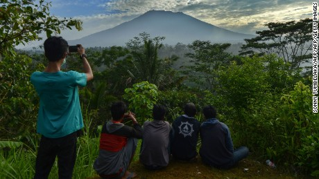 TOPSHOT - People look at Mount Agung in Karangasem on the Indonesian resort island of Bali on September 24, 2017.  Authorities have raised alert levels for a volcano on the Indonesian resort island of Bali after hundreds of small tremors stoked fears it could erupt for the first time in more than 50 years. / AFP PHOTO / SONNY TUMBELAKA        (Photo credit should read SONNY TUMBELAKA/AFP/Getty Images)