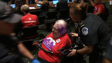A protester in a wheelchair is removed by police Monday, September 25, after protesters interrupted the Senate Finance Committee's hearing on a bill that would overhaul Obamacare.