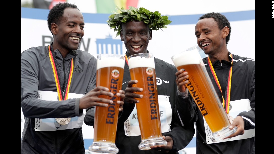 From left, Guye Adola, Eliud Kipchoge and Mosinet Geremew hold giant glasses of<br />beer Sunday, September 24, during the medal ceremony for the Berlin Marathon. Kipchoge, a Kenyan, won the race. Adola and Geremew, who are both Ethiopian, finished in second and third.