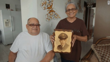 Miguel Olivera and his wife Diana Aponte show a picture from his time in service.