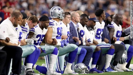 GLENDALE, AZ - SEPTEMBER 25: Members of the Dallas Cowboys link arms and kneel during the National Anthem before the start of the NFL game against the Arizona Cardinals at the University of Phoenix Stadium on September 25, 2017 in Glendale, Arizona.  (Photo by Christian Petersen/Getty Images)
