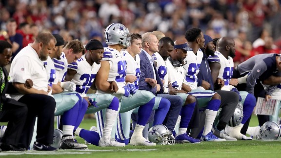 Members of the Dallas Cowboys link arms and kneel during the National Anthem before the start of the NFL game against the Arizona Cardinals on September 25, 2017 in Glendale, Arizona.