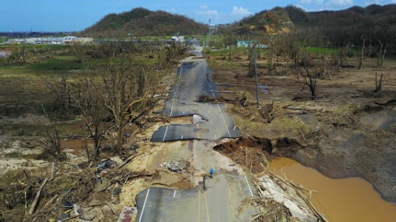 TOPSHOT - A man rides his bicycle through a damaged road in Toa Alta, west of San Juan, Puerto Rico, on September 24, 2017 following the passage of Hurricane Maria. Authorities in Puerto Rico rushed on September 23, 2017 to evacuate people living downriver from a dam said to be in danger of collapsing because of flooding from Hurricane Maria. / AFP PHOTO / Ricardo ARDUENGORICARDO ARDUENGO/AFP/Getty Images