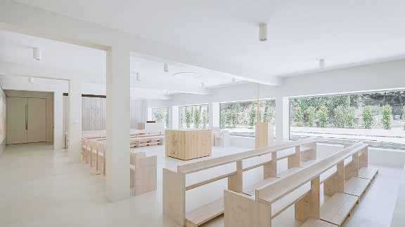 The interior was designed to create a simple place of worship and features simple wooden furniture and minimal decor.