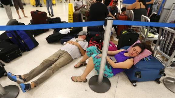 Stranded passengers rest Monday at San Juan