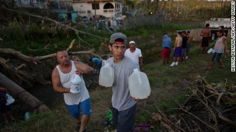 People carry water in bottles retrieved from a canal this week in Toa Alta, Puerto Rico.