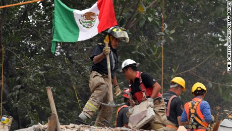 Mexican firefighters remove the debris from a multi-family building that collapsed during the 7.1-magnitud earthquake beside the Tlalpan road in Mexico City on September 26, 2017.  A week after an earthquake that killed more than 300 people, a shaken Mexico was torn Tuesday between trying to get back to normal and keeping up an increasingly hopeless search for survivors. / AFP PHOTO / YURI CORTEZ        (Photo credit should read YURI CORTEZ/AFP/Getty Images)
