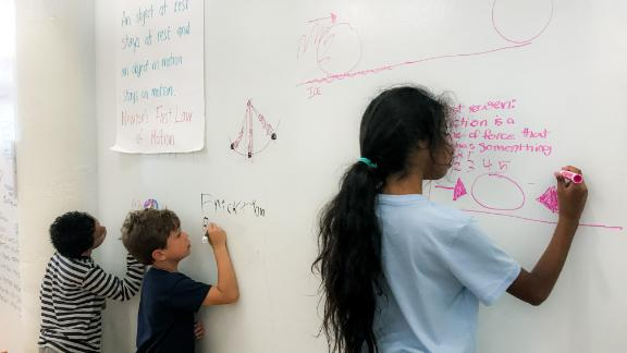 Children independently problem solve on walls made of whiteboards.