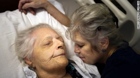 "Alexandra ""Alex"" Carington, 63, with her mother Lenore Greenfield, 88, at the Holiday Manor Care Center, a nursing facility in Canoga Park, California. Alexandra prepares Lenore for an afternoon nap."