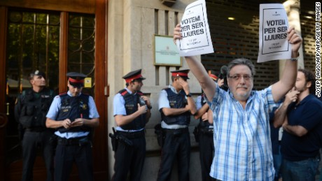 "A man holds pro-referendum posters reading in Catalan ""Vote to be free"" as Spanish Civil Guards and Catalan regional police officers 'Mossos D'Esquadra"" stand in front of the Economy headquarters  of Catalonia's regional government in Barcelona on September 20, 2019, during a search by Spain's Guardia Civil police.   The operation comes amid mounting tensions as Catalan leaders press ahead with preparations for an independence referendum on October 1 despite Madrid's ban and a court ruling deeming it illegal.   / AFP PHOTO / Josep LAGO        (Photo credit should read JOSEP LAGO/AFP/Getty Images)"