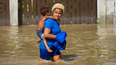 Local residents wade through the flooded streets of Arenoso, northeastern Dominican Republic, on September 24, 2017 after the passage of Hurricane Maria. 