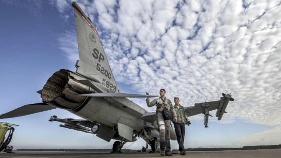 An Air Force pilot and crew chief conduct a pre-flight inspection at a base in Krzesiny, Poland, on Monday, September 11.