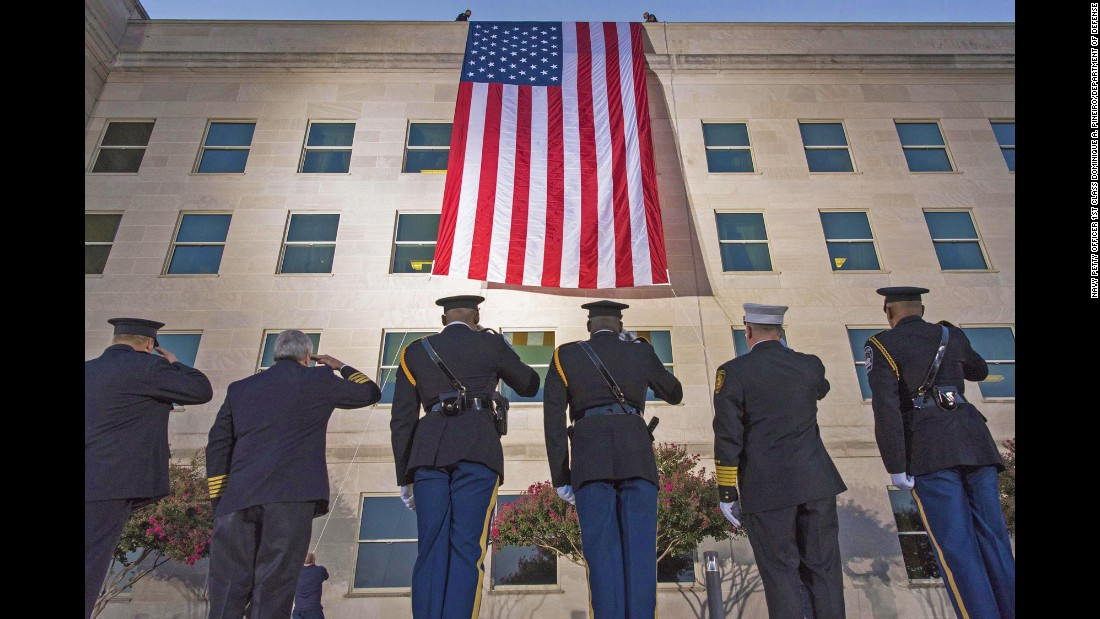 "First responders salute a large American flag as it's unfurled over the west side of the Pentagon on Monday, September 11. <a href=""http://www.cnn.com/2017/08/31/politics/gallery/us-military-august-photos/index.html"" target=""_blank"">See US military photos from August</a>"