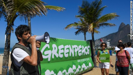 Brazil's Greenpeace Campaign Director Nilo Davila speaks on a loudspeaker during a demonstration against the government decision to scrap a huge Amazon reserve and allow commercial mining, at Ipanema beach in Rio de Janeiro, on August 27, 2017.  Brazil's President Michel Temer's decision issued last week scrapped a national reserve in the northern Para and Amapa states that had protected a 17,800 square mile (46,000 square km) area since 1984, when Brazil was still run by a military dictatorship. / AFP PHOTO / Apu Gomes        (Photo credit should read APU GOMES/AFP/Getty Images)