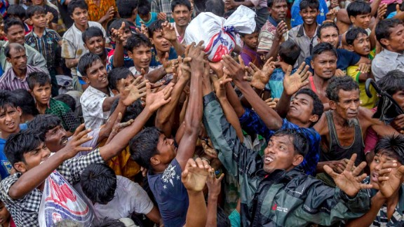 People scramble to catch food distributed by aid groups on September 18 at the Balukhali refugee camp in Bangladesh.