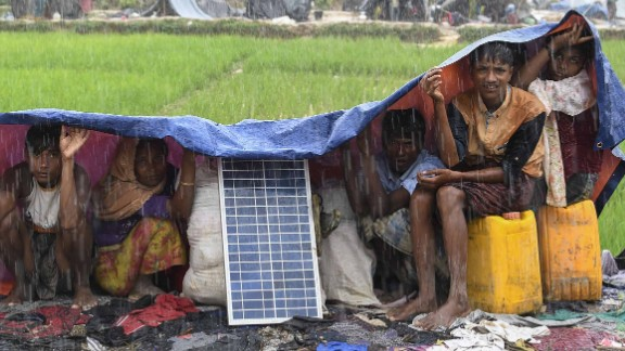 Rohingya refugees take cover from monsoon rains on September 17 in the Balukhali refugee camp in Bangladesh.