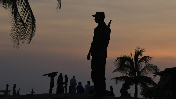 A Bangladeshi border guard keeps watch September 16 near the beach of Sharapuri Dwip, where many Rohingya refugees land after crossing from Myanmar.