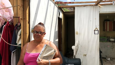 Julia Rivera, a school secretary, standing in her home which now has no roof.