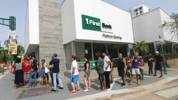 Long lines are a familiar sight in Puerto Rico. Here people wait to withdraw cash from a San Juan bank.
