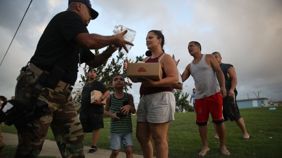TOA BAJA, PUERTO RICO - SEPTEMBER 28: Sgt. Nelson Sierra of the municipal police hands out food and water to hurricane survivors as he and volunteers  deal with the aftermath of Hurricane Maria on September 28, 2017 in Toa Baja, Puerto Rico.  Puerto Rico experienced widespread damage including most of the electrical, gas and water grid as well as agriculture after Hurricane Maria, a category 4 hurricane, passed through.  (Photo by Joe Raedle/Getty Images)