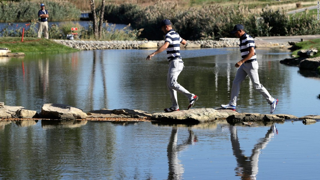 Avoiding the drink. Thomas, left, and Fowler, right, walk to the 13th hole during their foursomes match.