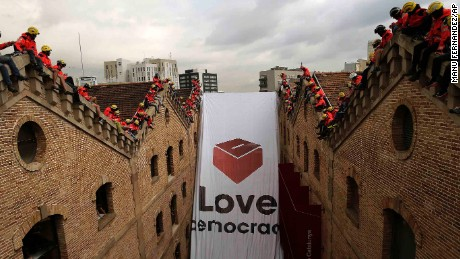 "Catalan firefighters unfold a banner with a ballot box and the words ""Love democracy"" at the Museum of History of Catalonia in Barcelona on Thursday."