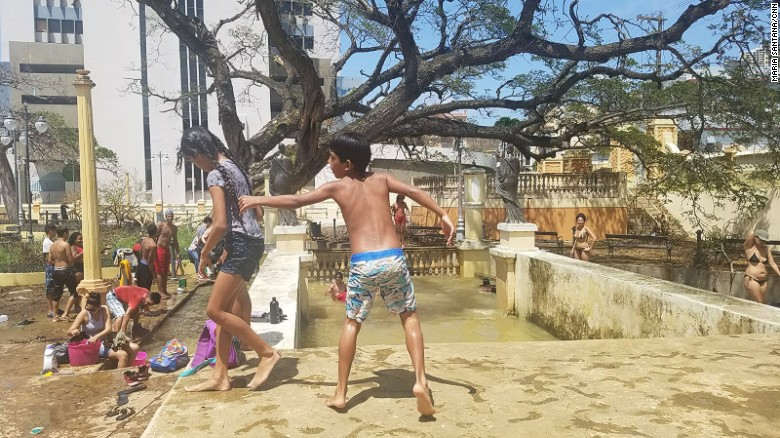 Puerto ricos west side no signs of fema cnn children bathe in the water from a flooded plaza in aguadilla a coastal town in publicscrutiny Image collections