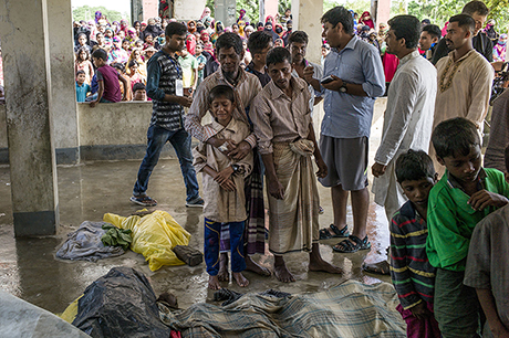 Rohingya refugees mourn beside the bodies of relatives who died when a boat capsized. (Fred Dufour/AFP/Getty Images)