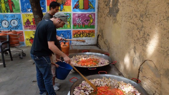 Volunteers cook giant dishes of paella to feed those occupying one Barcelona school on Saturday.