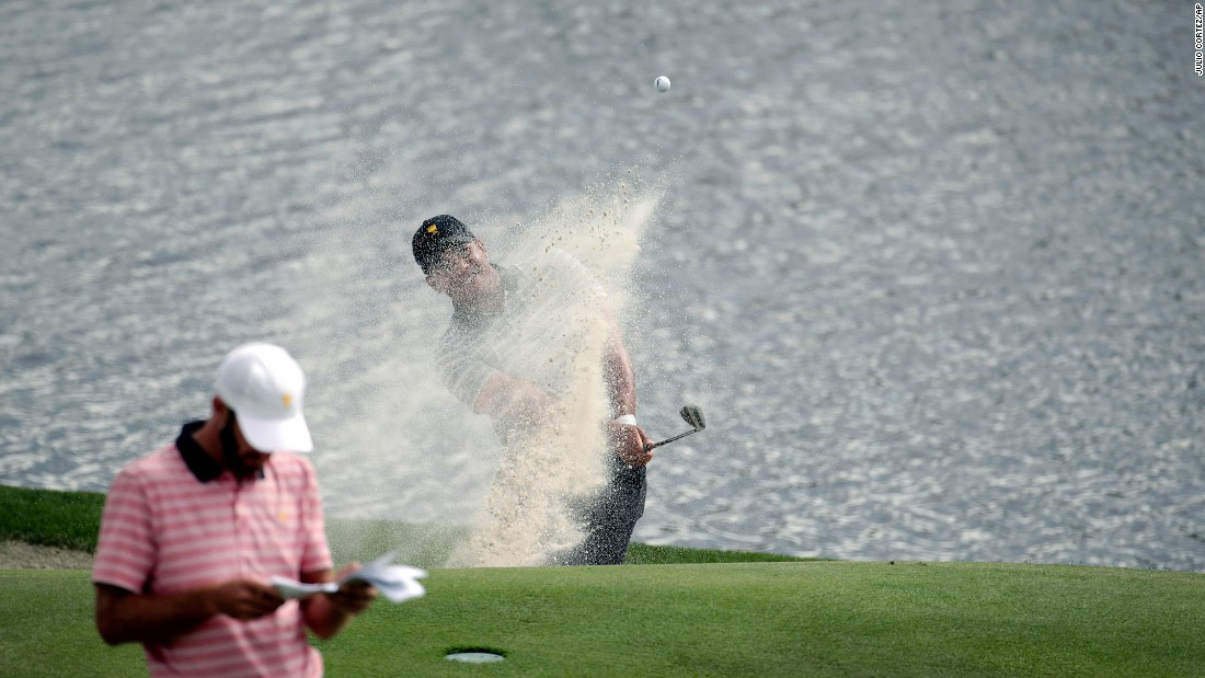Jhonattan Vegas, rear, hits from a bunker as Dustin Johnson, left, waits on the seventh green during the four-ball golf matches on the second day of the Presidents Cup at Liberty National Golf Club in Jersey City, N.J., Friday, Sept. 29, 2017. (AP Photo/Julio Cortez)