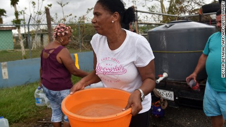 A woman carries water taken from a tank in Vega Baja, Puerto Rico, on September 30, 2017, due to the lack of water after the passage of Hurricane Maria. US military and emergency relief teams ramped up their aid efforts for Puerto Rico amid growing criticism of the response to the hurricanes which ripped through the Caribbean island. / AFP PHOTO / HECTOR RETAMAL        (Photo credit should read HECTOR RETAMAL/AFP/Getty Images)